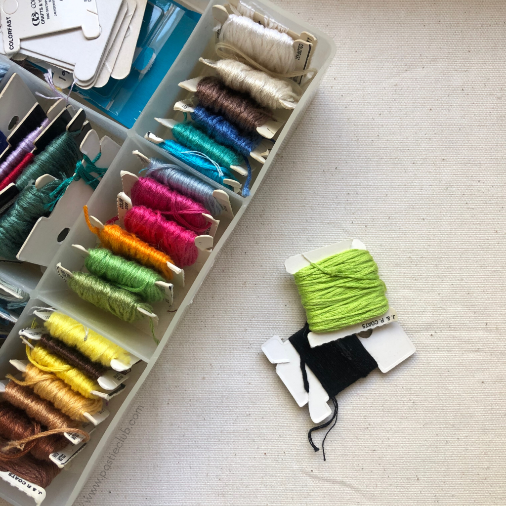 a flat lay of an embroidery box thread full of different colored threads
